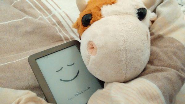 Tolino Shine im Bett eingemummelt mit Plüschkuh